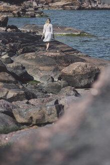 Rear view of woman in white dress walking along rocky beach - FOLF08009
