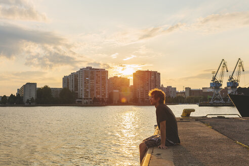 Man sitting on pier at sunset - FOLF08075