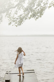 Girl standing on jetty by lake - FOLF08461