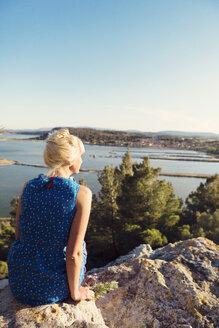 Woman sitting on rocks overlooking bay - FOLF08482