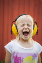 Portrait of blonde girl wearing ear muffs, screaming with eyes closed - FOLF08569