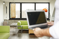 Businessman holding laptop, punch bag in the background - PESF01015