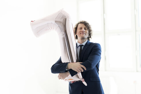 Proud businessman holding a No 1 balloon - HHLMF00163