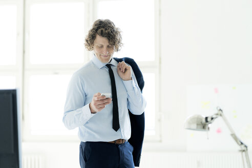 Smart businessman standing in office, using mobile phone - HHLMF00178