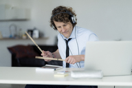 Businessman wearing headphones and drumming on his desk - HHLMF00184