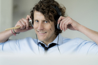 Businessman wearing headphones, holding drum sticks - HHLMF00187