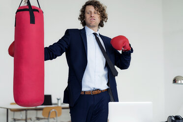 Stressed businessman hitting punch bag with boxing gloves in his office - HHLMF00202