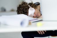 Overworked businessman sleeping at his desk wearing a sleeping mask - HHLMF00220