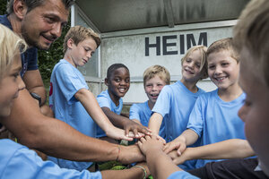 Coach and young football players huddling - WESTF24033