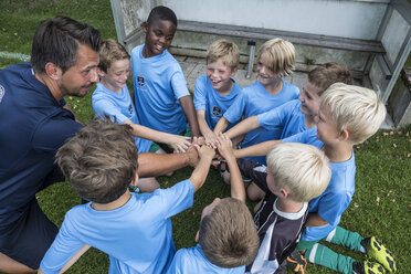Coach and young football players huddling - WESTF24036