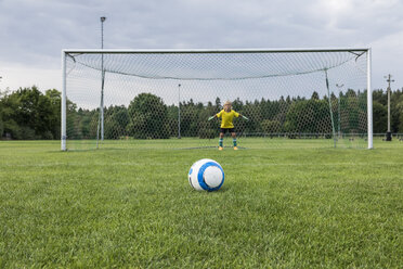 Young football goalkeeper with ball on football ground - WESTF24039
