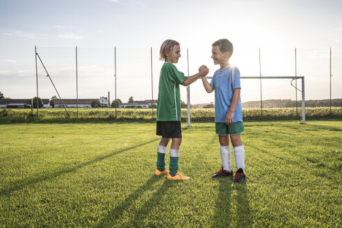 Smiling young football players shaking hands on football ground - WESTF24045