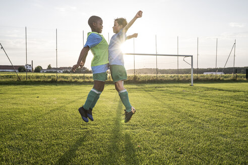 Young football players jumping on football ground - WESTF24048