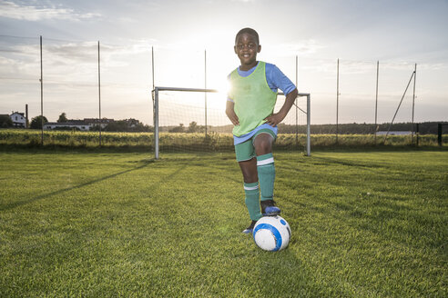 Portrait of confident young football player with ball on football ground - WESTF24051