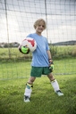 Portrait of smiling young football goalkeeper holding ball on football ground - WESTF24057