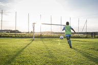 Young football player on football ground at sunset - WESTF24060