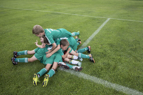Germany, young football players lying on top of each other - WEST24064