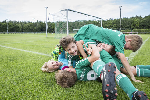 Germany, young football players lying on top of each other - WEST24070