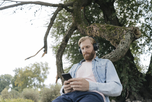 Man with smartphone and headphones listening music outdoors - KNSF03661