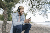 Germany, Duesseldorf, smiling man with headphobnes using smartphone on the beach - KNSF03664