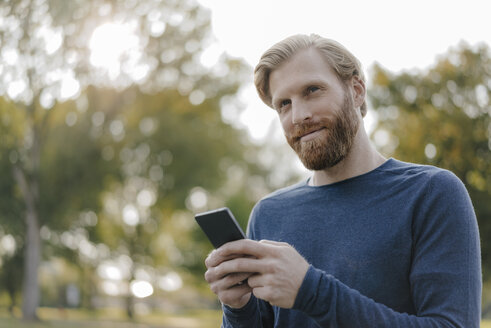 Portrait of man using cell phone in a park - KNSF03679