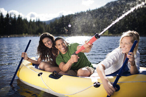 Man spraying water with squirt gun while sitting by female friends in raft - CAVF33945