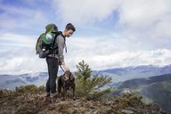 Woman standing with dog on mountain cliff against cloudy sky - CAVF33987