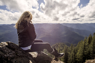 Woman sitting on rock at mountain cliff against cloudy sky - CAVF33996
