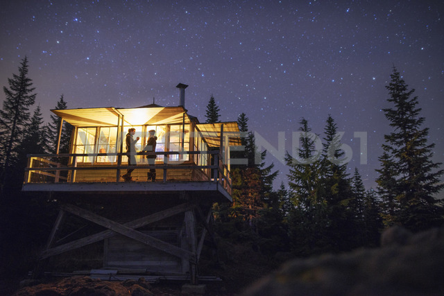 Low angle view of women standing in illuminated cottage at night - CAVF34017