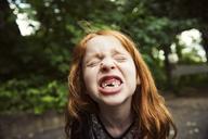 Close-up of girl clenching teeth at park - CAVF34095