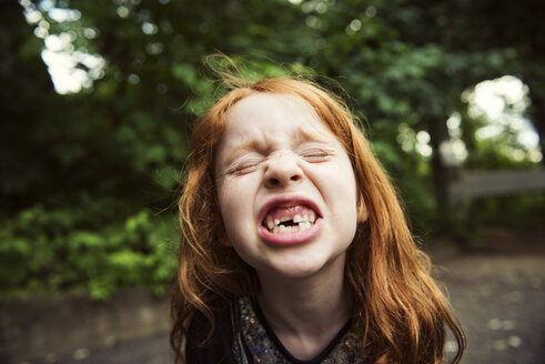 Close-up of girl clenching teeth at park - CAVF34095