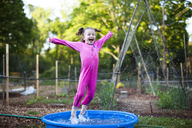 Cheerful girl jumping in wading pool on field - CAVF34167