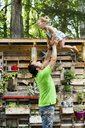 Playful father throwing daughter in air while standing at backyard - CAVF34173
