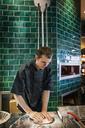 Male chef preparing pizza dough in commercial kitchen - CAVF34194