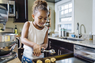 Girl preparing chocolate chip cookies in kitchen - CAVF34206