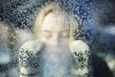 Close-up of woman with eyes closed seen through glass during winter - CAVF34273