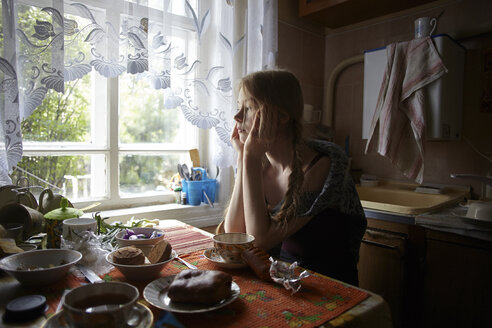 Thoughtful woman with hands on chin looking away while sitting by table at home - CAVF34282