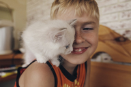 Side view of happy boy with cat on shoulder - CAVF34288