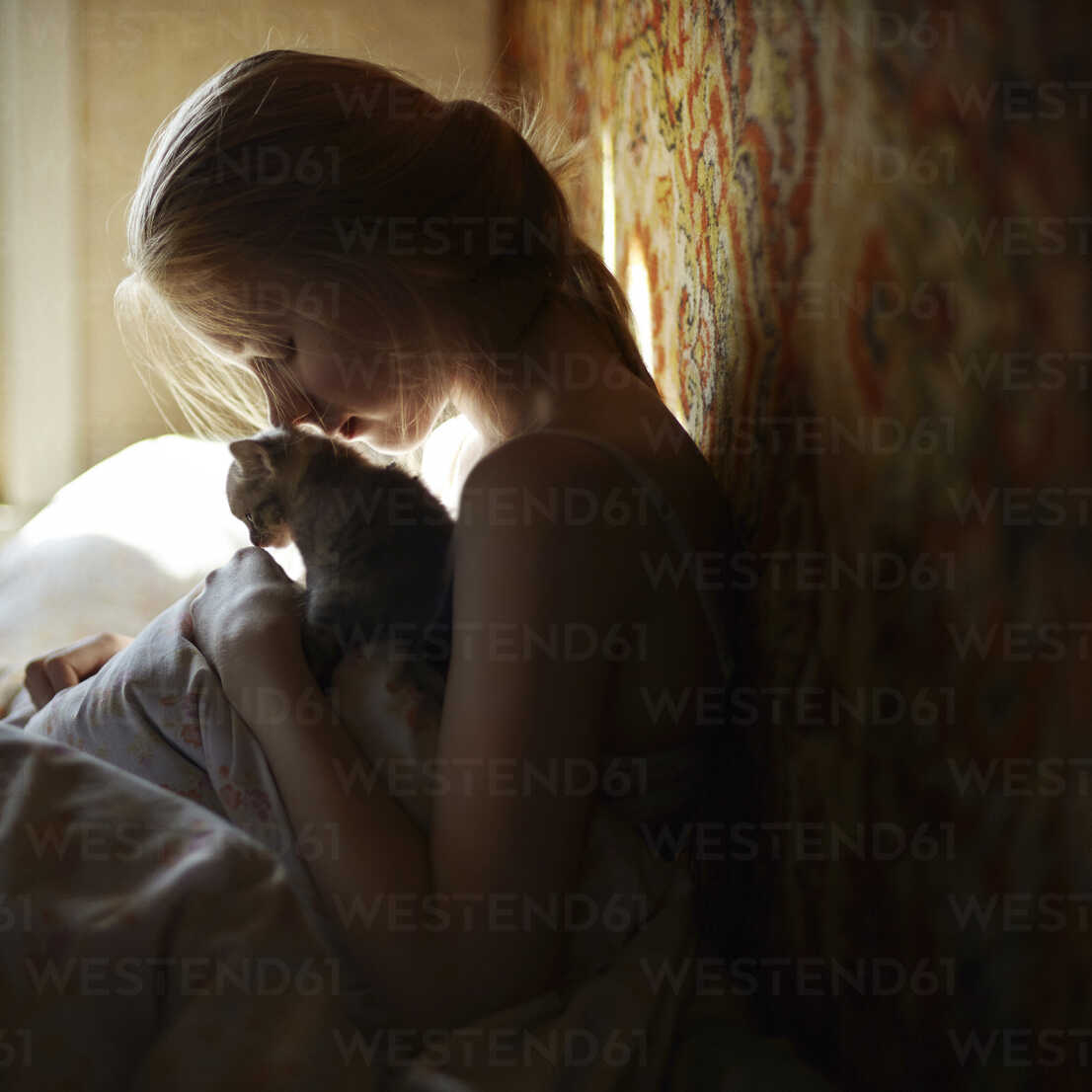 Side view of woman sitting with cat on bed - CAVF34309 - Cavan Images/Westend61
