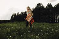 Rear view of woman wearing poncho walking on grassy field against sky - CAVF34312