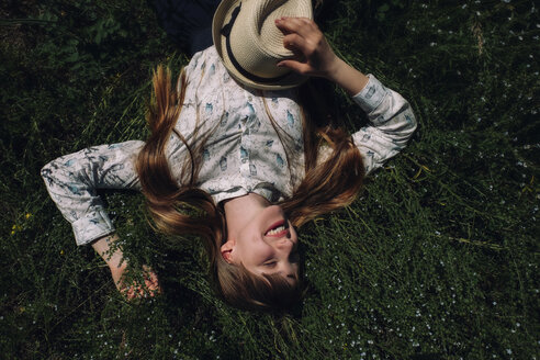 High angle view of happy woman lying on field - CAVF34327