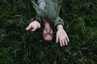 Overhead portrait of happy woman lying on grassy field - CAVF34336