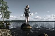 Full length of woman standing on rock in river against cloudy sky - CAVF34351