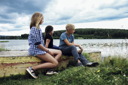 Siblings looking at view while sitting on retaining wall at lakeshore against stormy clouds - CAVF34354
