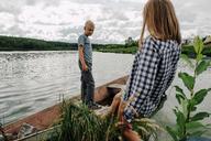Brother looking at sister walking into rowboat - CAVF34360