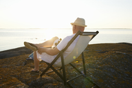 Mature man relaxing in lounge chair on rocky beach - FOLF09226