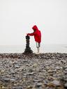 Boy building cairn on beach - FOLF09274