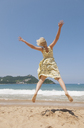 Woman jumping on beach, looking at Bay of Biscay in Spain - FOLF09412