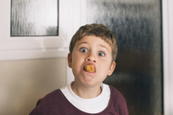 Portrait of boy with food in mouth pulling faces - SKCF00395