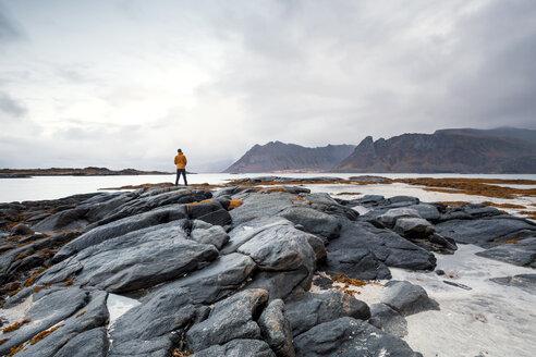 Norway, Lofoten Islands, Gimsoysand, man standing at rocky coast - WVF00929